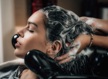 Hairdresser applying shampoo on woman's hair in beauty salon.