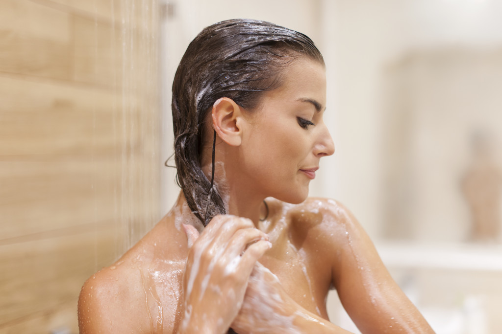 Woman washing hair under shower